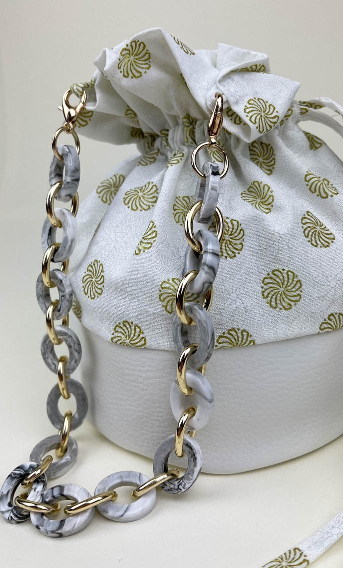 Borsa aria in stoffa shweshwe con fondo in ecopelle bianco e catena color oro, bianco e nero come manico scatto 3