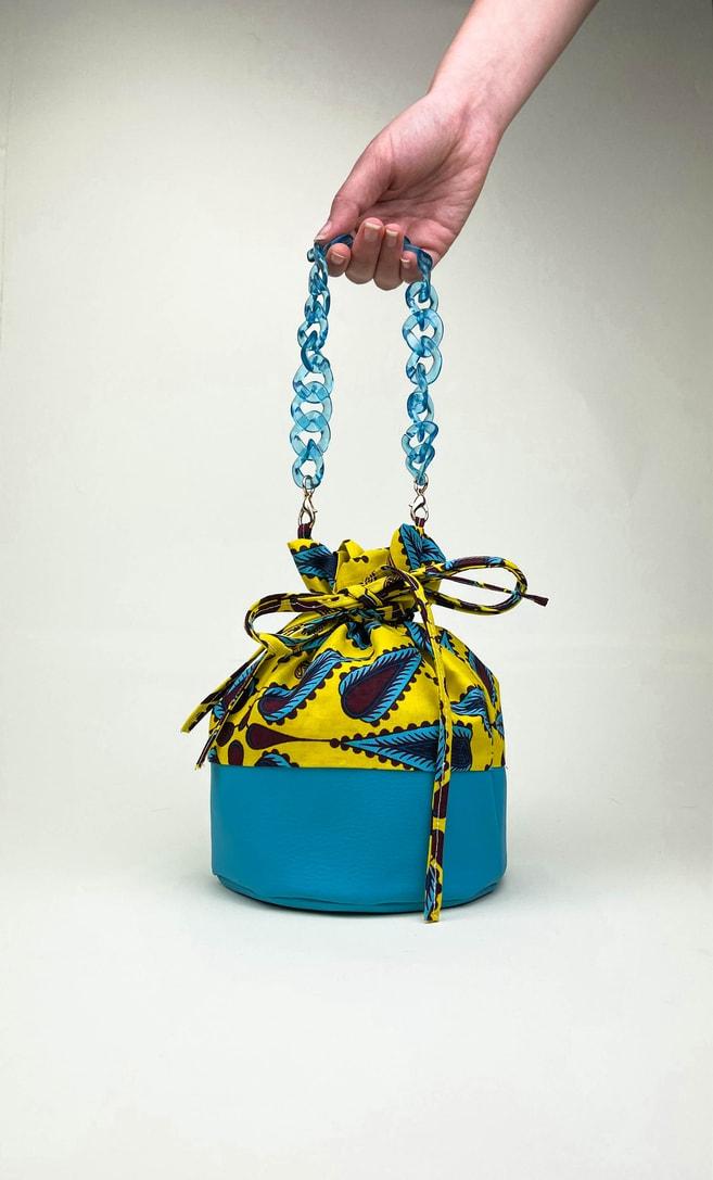 Borsa limone in stoffa wax con fondo in ecopelle turchese e catena in azzurro come manico e ganci color oro scatto 1