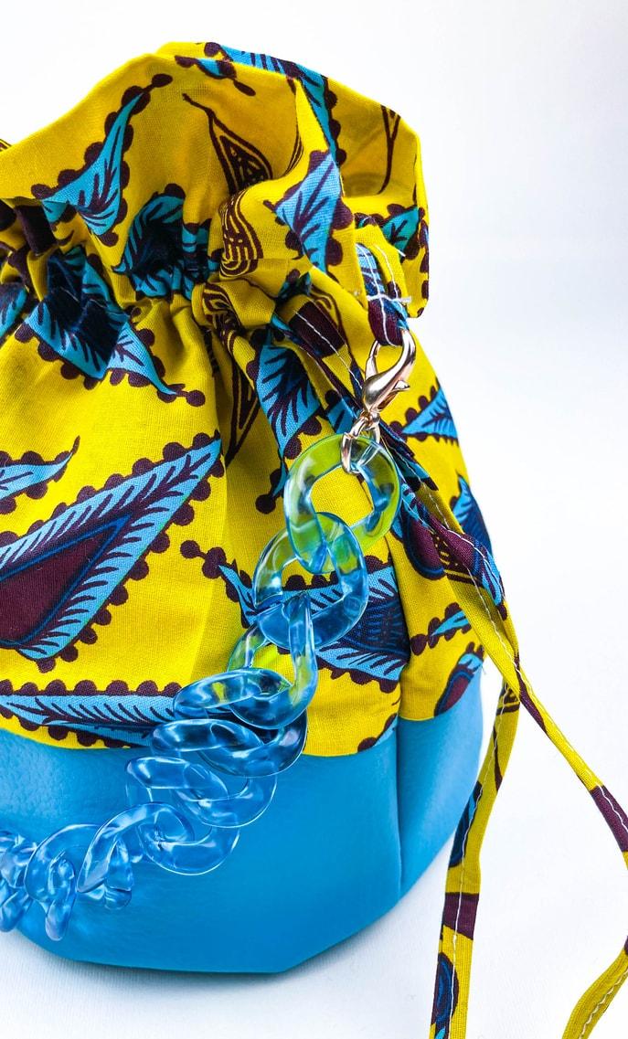 Borsa limone in stoffa wax con fondo in ecopelle turchese e catena in azzurro come manico e ganci color oro scatto 3
