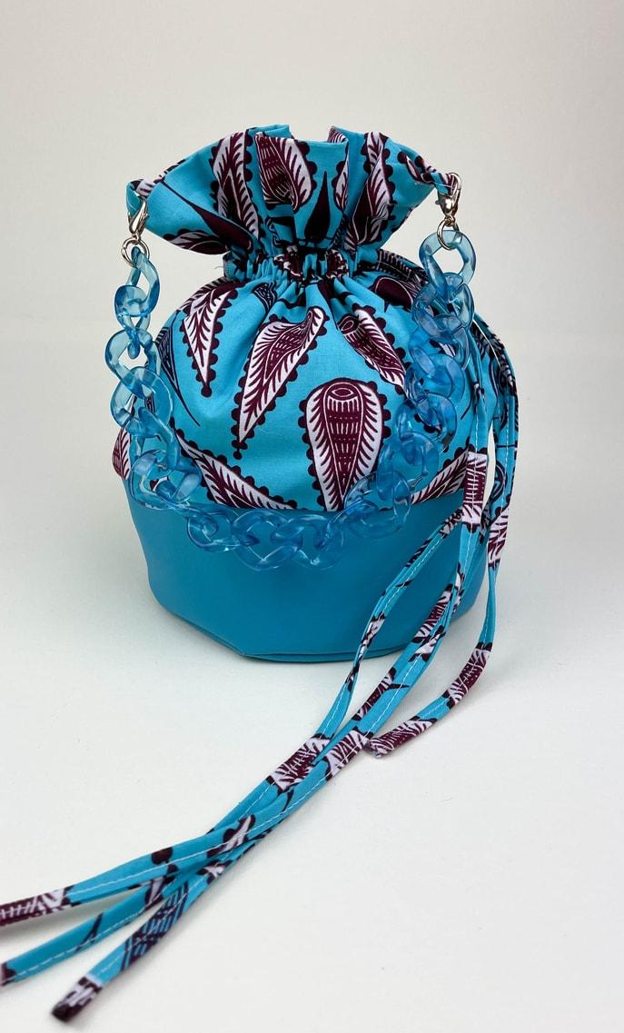 Borsa turchese in stoffa wax con fondo in ecopelle turchese e catena in azzurro come manico e ganci color oro scatto 2