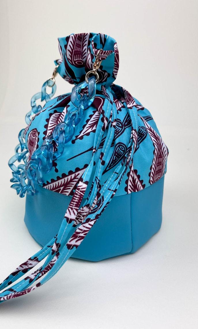 Borsa turchese in stoffa wax con fondo in ecopelle turchese e catena in azzurro come manico e ganci color oro scatto 3