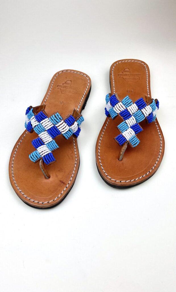 Sandalo topazio in cuoio con perline bianche, azzurre e blu che adornano la parte superiore scatto 1
